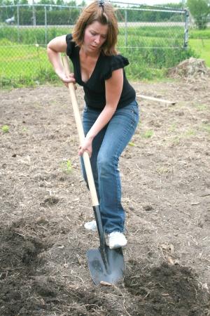 Een jonge vrouw is het graven van de aarde in de tuin Stockfoto