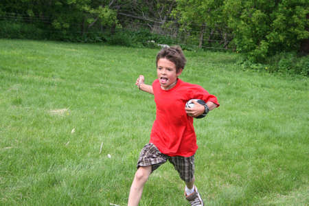 A young boy is playing touch football