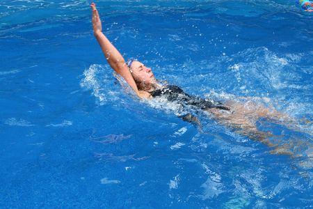 Girl doing a backstroke in a pool