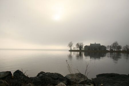 View of monastery on a  foggy lake  in fall