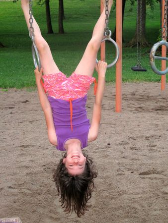 Young girl hanging upside down photo