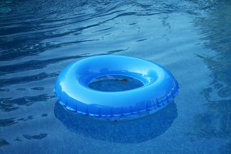A blue inflatable tire floating in the pool