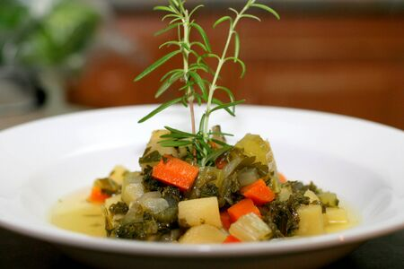 Bowl of kale and vegetable soup with rosemary Stockfoto