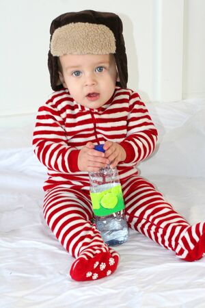 Baby boy with winter hat and red stripe pyjama