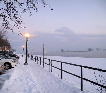 lamplight: Lamplight on  waterfront  with low lying fog in winter                                Stock Photo