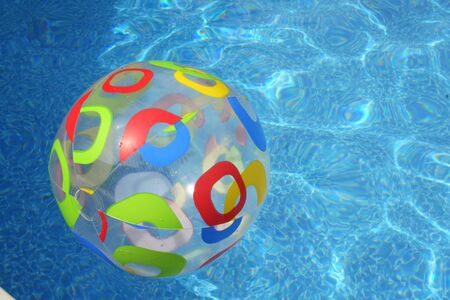 Colorful beach ball floating on top of the pool
