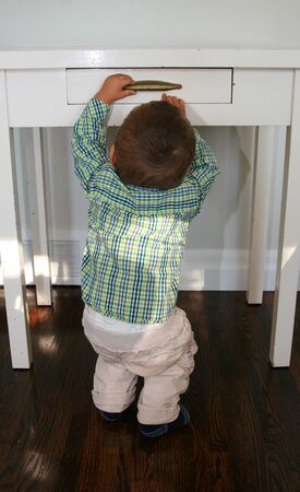 Baby boy in plaid shirt opens a drawer of a  white table