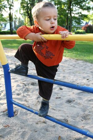 Baby boy climbing up a metal bar in a park photo