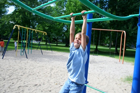Boy in blue jeans swinging from a bar in a park  Stock Photo - 14012430