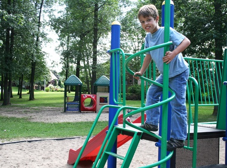 Boy in blue jeans climbing a round pole in  playground