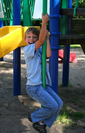 Boy in blue jeans sliding down a pole in a park Stock Photo - 14012370