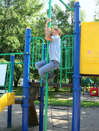 Boy in blue jeans sliding down a pole in a park Stock Photo - 14012438
