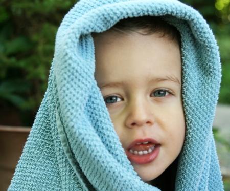 青いタオルで覆われた頭で愛らしい男の子