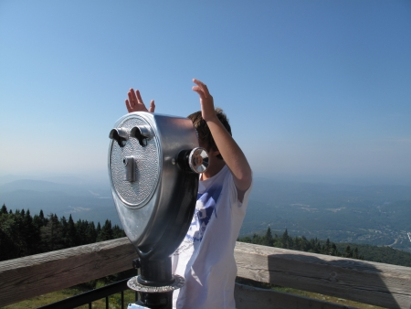 Boy with raised arms at a lookout
