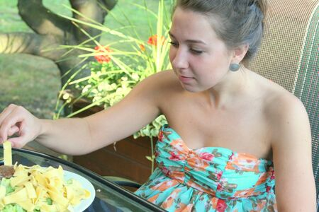 strapless: Pretty girl in strapless dress eating dinner from a plate Stock Photo