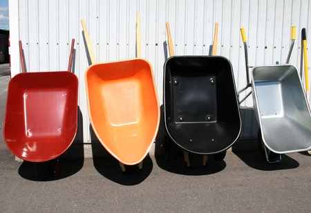 Four colorful wheelbarrows lined up against a metal wall