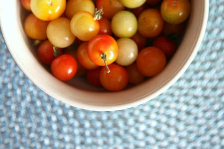 Multi-colored cherry tomatoes in a bowl on a blue mat Stock Photo