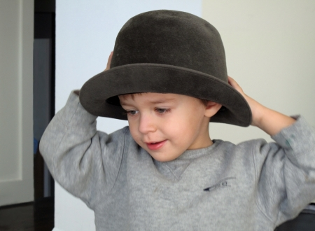 Toddler with old grey felt  hat                             photo