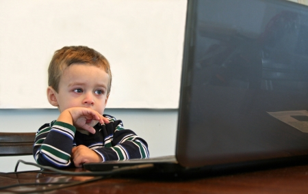 Toddler with striped shirt looking at computer