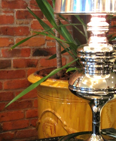 Decor of lamp and yellow planter with brick baqckground
