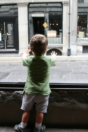 window view: Toddler looking out the window on the street and stores  Stock Photo