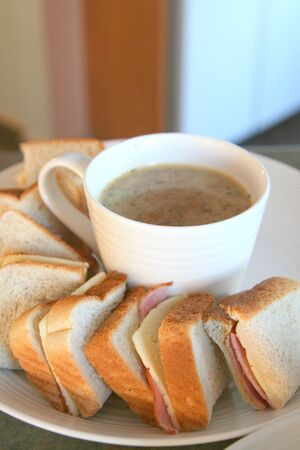 Sandwiches and white cup of soup on a white plate