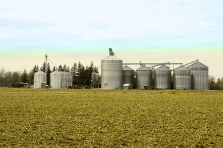Metal grain silos for crop drying on a farm Stock Photo