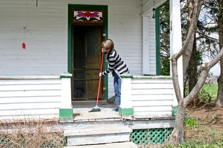 Woman sweeping front porch Stock Photo