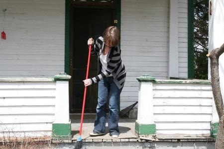 front porch: Mujer barriendo porche Foto de archivo