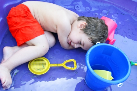 Toddler lying down in a pool with his toys