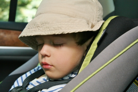 Little boy with cap sleeping in a car seat