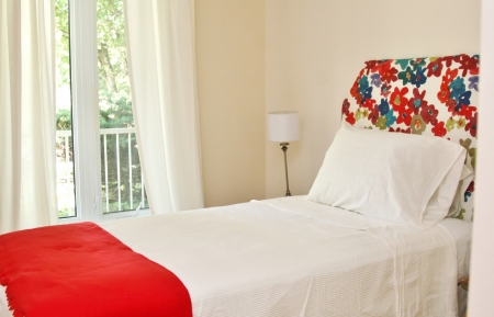 Colorful headboard with lamp and red blanket