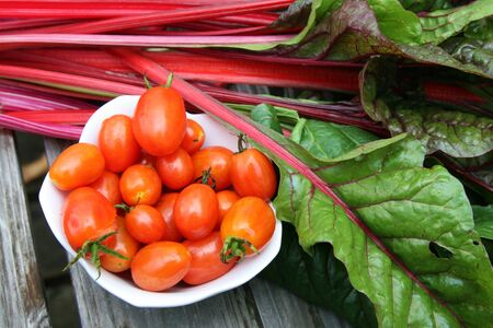 Harvest of cherry tomatoes in white bowl and swiss chard Stock Photo
