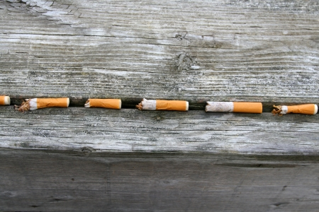 Dirty smoked cigarette butts in a line