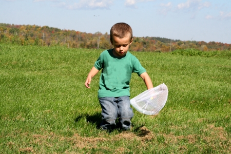 Toddler chasing butterflies with net Stock Photo