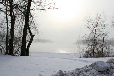 Winter scene with snow and fog on lake