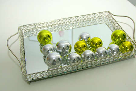 Silver and chartreuse Xmas balls on mirrored tray Stock Photo