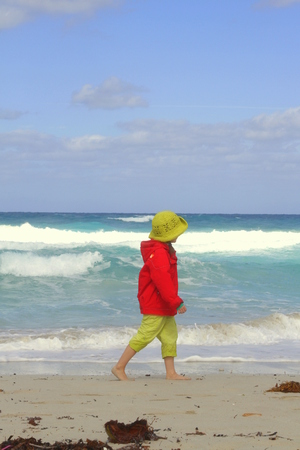 Little girl with cap and red jacket walks on the sandy beach Stock Photo