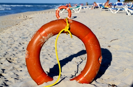 Row of round life preservers in the sand Stock Photo