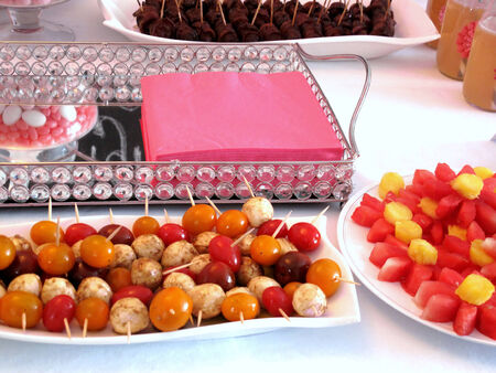 Food platters of boccancini and cherry tomatoes, sausages wrapped in bacon, watermellon flowers, and serviettes