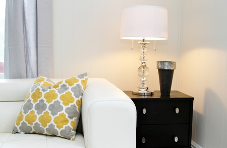 Room decorated with white leather sofa, black end table, lamp with glass stand, metal vase