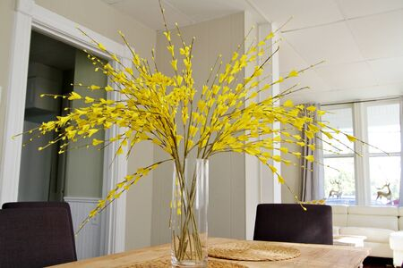 Long yellow flower branches in glass vase on table