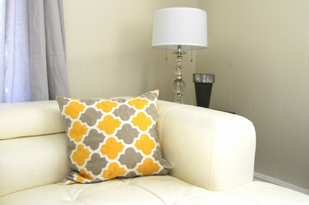 Decorator corner with white leather sofa, lamp with glass stand, metal vase