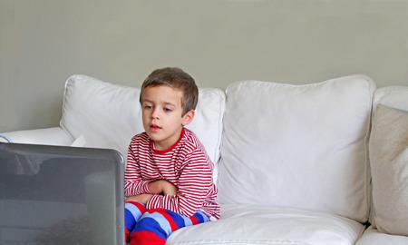 Boy with pyjamas sitting on white sofa Stock Photo