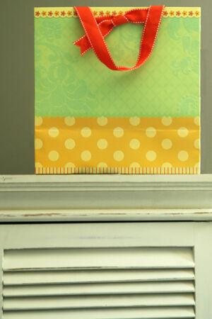 Colorful gift bag on  white dresser