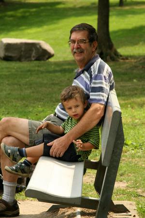Grandpa and grandson sitting on park bench