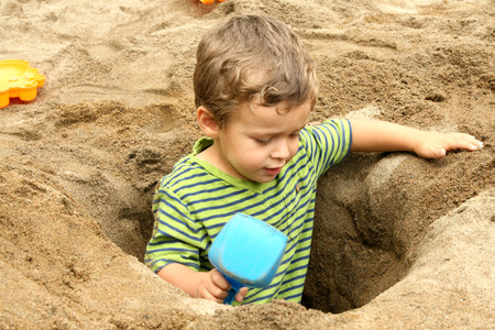 Small boy in a dug out sand hole with shovel