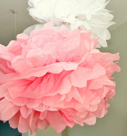 Pink and white pompoms hanging from a ceiling Stock Photo