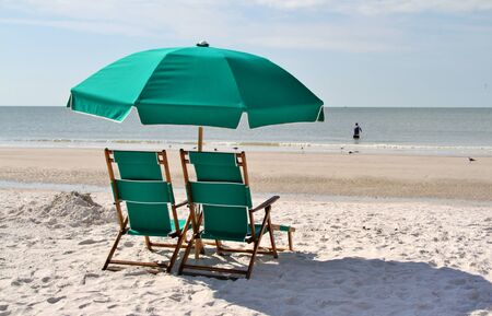 Green sun chairs and umbrella on a beach of an ocean