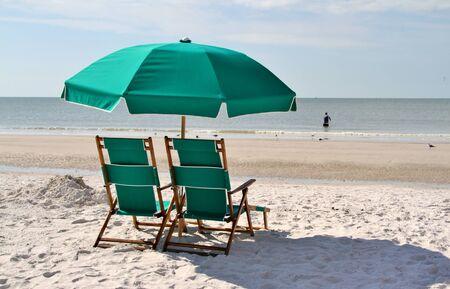 Green sun chairs and umbrella on a beach of an ocean